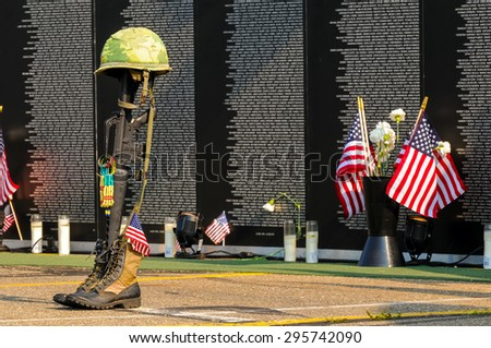 TWINSBURG, OH, USA - JULY 4, 2015: A fallen soldier tribute stands before panels of a replica Vietnam Memorial Wall, on tour with the Cost of Freedom tribute, a traveling veterans-based exhibit - stock photo