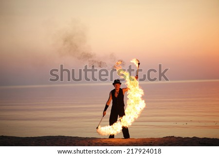 Twirling fire torch on the beach - stock photo