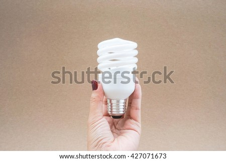 Twist and spiral LED light bulb in hand with brown background