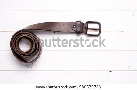 twisted brown male leather belt on wooden background, top view