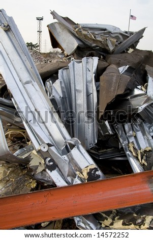 Twisted Metal from Destroyed Building with Flag in Background - stock photo