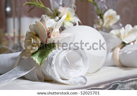 Twisted napkin decorated with flowers lies on the holiday table - stock photo