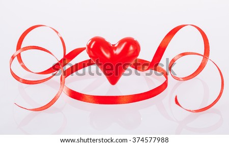 Twisted red ribbon and ceramic heart on neutral background