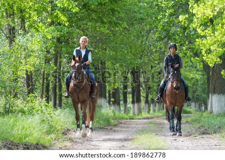 Two a young girls on horseback riding - stock photo