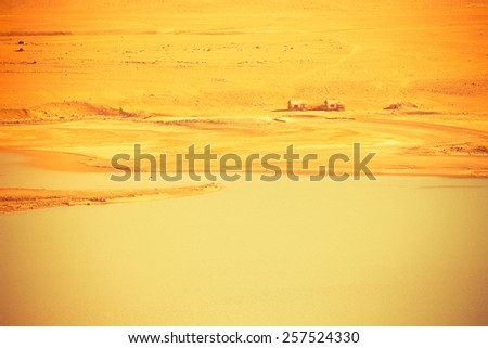 Two abandoned houses on the shore of a clean mountain lake in a dry rocky valley. Toned orange. - stock photo