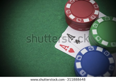 two Ace of pokers beside lots of chips on casino table - stock photo