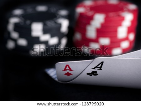 two aces high on black table with chips on black background - stock photo
