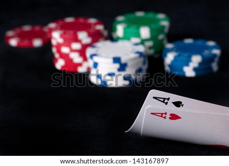 two aces high on black table with chips on black background