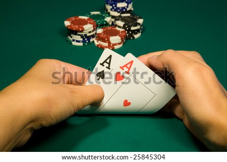 Two aces in hand in game poker on the green casino table - stock photo