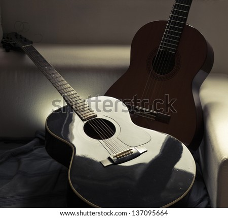 Two acoustic guitars on a couch - stock photo