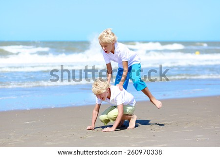 Two active laughing boys, teenage twin brothers, playing, running and jumping on the beach enjoying together sunny summer vacation day in camping at the sea - stock photo