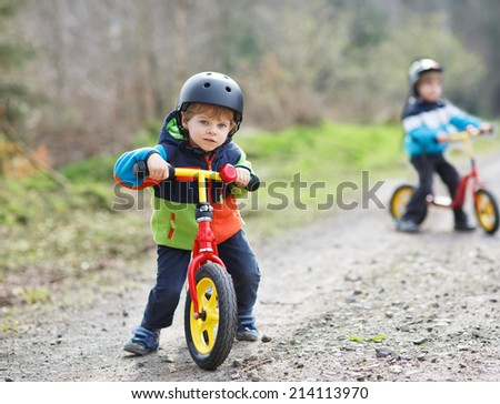 Two active little sibling boys having fun on bikes in forest on cold day. - stock photo