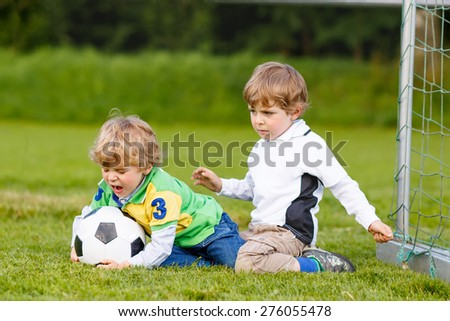 Two active twins playing soccer and football and having fun on field, outdoors. Active leisure with children on warm sunny summer day. - stock photo