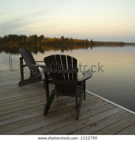 Two Adirondack Chairs on Dock - stock photo