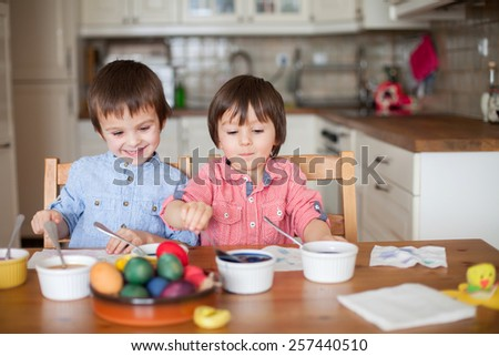Two adorable boys, coloring eggs for Easter at home, having fun - stock photo