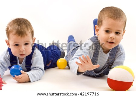 two adorable boys enjoy with colorful balls