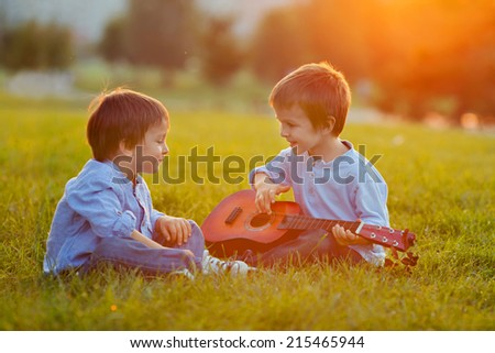 Two adorable boys, sitting on the grass, playing guitar on sunset - stock photo