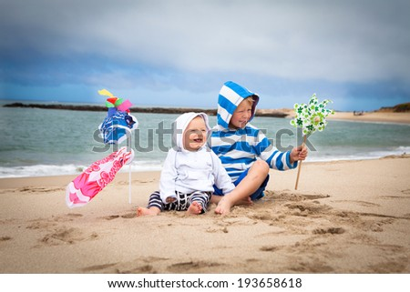 Two adorable brothers playing with windsocks and pinwheel on the beach  - stock photo