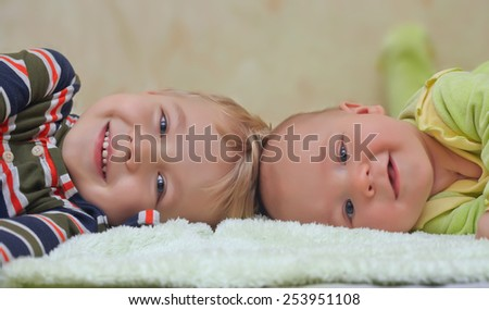 Two adorable brothers smiling on a bed - stock photo