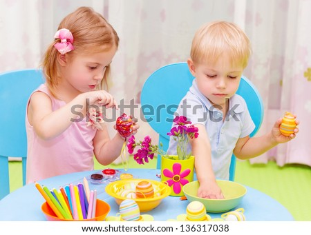 Two adorable children paint Easter eggs in kindergarten, drawing lessons, colorful decorations, traditional Eastertime art - stock photo
