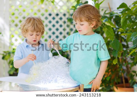 Two adorable friend boys making experiment with colorful soap bubbles and water, outdoors. On warm sunny day children playing together. Creative leisure with kids in summer, outdoors.Child development - stock photo