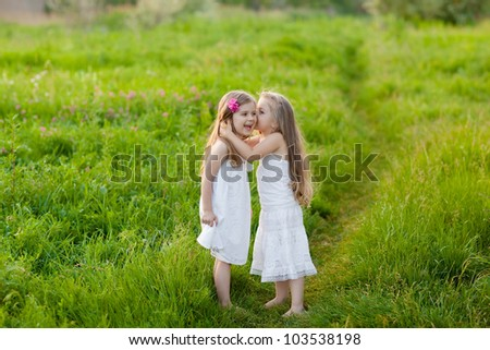Two adorable girl in white dresses playing on the meadow