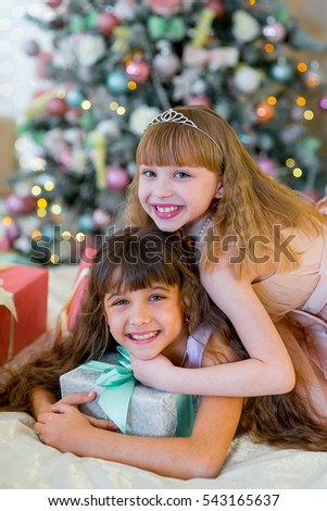 Two adorable girls in a white dress lying on the bed between Christmas gifts