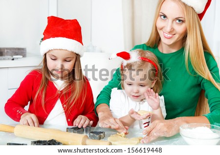 Two adorable girls with her mother baking Christmas cookies in the kitchen