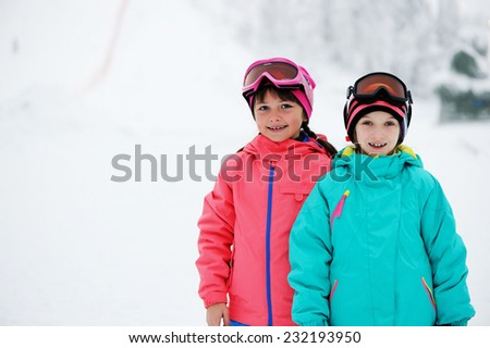 Two adorable kid girls in warm colorful clothes and ski goggles near the slopes in the winter - stock photo