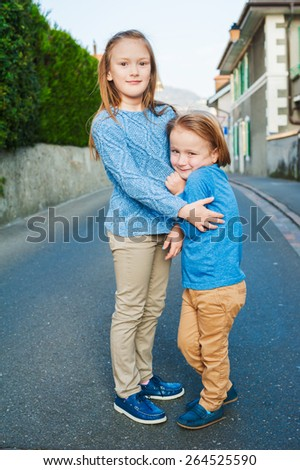 Two adorable kids in a city, girl and her little brother, wearing blue and beige clothes and moccasins - stock photo