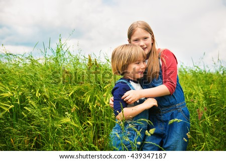 Two adorable kids, little girl and boy, playing in green wheat field. Sweet children having fun in summertime