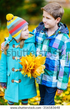 Two adorable kids outdoors in a beautiful park at sunny autumn day - stock photo