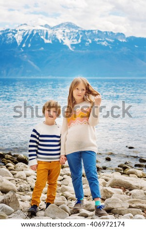 Two adorable kids playing by the lake, little girl and her brother having fun outdoors on a nice spring day