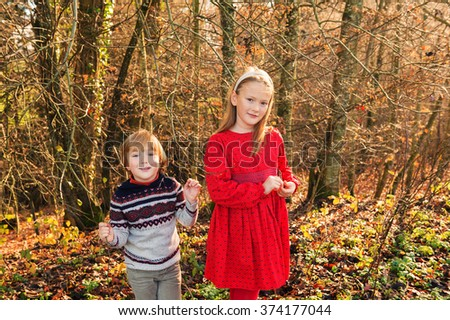 Two adorable kids plying in autumn forest on a warm sunny day. Brother and sister having fun outdoors - stock photo