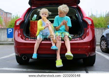 Two adorable kids, teenager boy and funny preschooler girl, brother and sister, sitting in the trunk of modern red car eating bread enjoying family weekend shopping in supermarket - stock photo