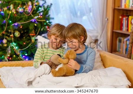 Two adorable little blond kid boys, twins playing with soft toys together in bed near Christmas tree with lights and illumination. Happy family, two children and friends. - stock photo