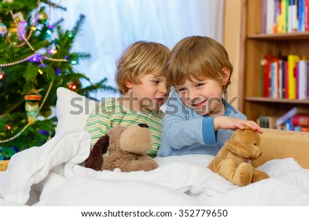 Two adorable little blond kid boys, twins playing with soft toys together in bed near Christmas tree with lights and illumination. children enjoying xmas morning with gifts. - stock photo