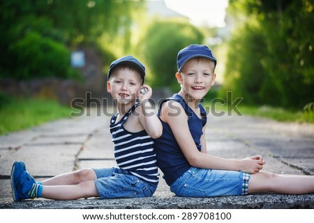 Two adorable little brothers sitting on stone on warm and sunny summer day. Sitting back to back, looking at the camera - stock photo