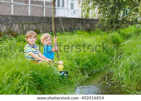 Two adorable little friends  fishing on a river with selfmade fishing rod  on sunny summer day. Happy children having fun. Active leisure for children outdoors. - stock photo