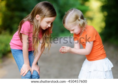 Two adorable little girl catching babyfrogs on warm and sunny summer day - stock photo