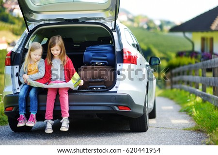 Two adorable little girls ready to go on vacations with their parents. Kids sitting in a car examining a map. Traveling by car with kids.