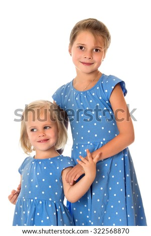 Two adorable little girls sisters older and younger age in the same blue dresses with polka dots-Isolated on white background - stock photo