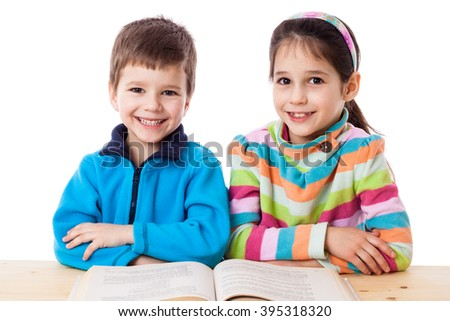Two adorable little kids reading the book, isolated on white - stock photo