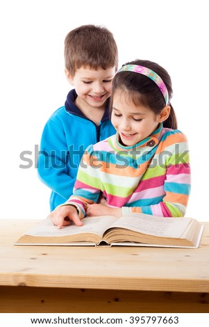 Two adorable little kids reading the book together, isolated on white