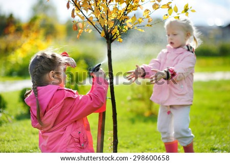 Two adorable little mommy's helpers watering plants in the garden on beautiful autumn day - stock photo