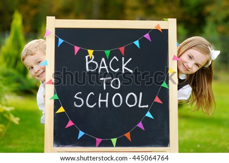 Two adorable little schoolkids feeling very excited about going back to school - stock photo