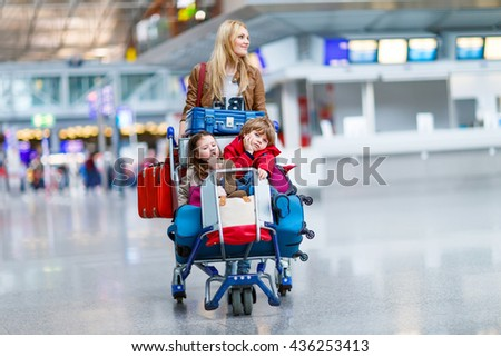 Two adorable little siblings, kid boy and girl sitting on suitcases on international airport. Young mother pushing. Brother and sister, happy family wating for flight and going on vacations.