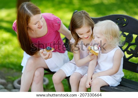 Two adorable little sisters and their mother sharing delicious cream tart outdoors on a beautiful and warm summer day - stock photo