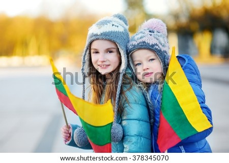 Two adorable little sisters celebrating Lithuanian Independence Day holding tricolor Lithuanian flags in Vilnius - stock photo
