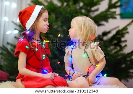 Two adorable little sisters decorating a Christmas tree at home - stock photo